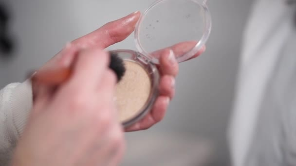 Nő van gyűjtő por egy kefe make-up, a közeli képe