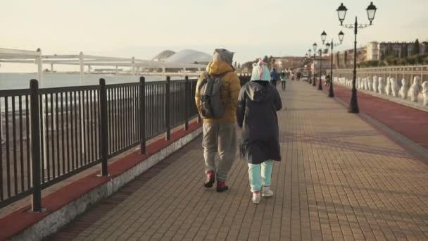Couple of young people are wearing kigurumi and coats, walking over embankment