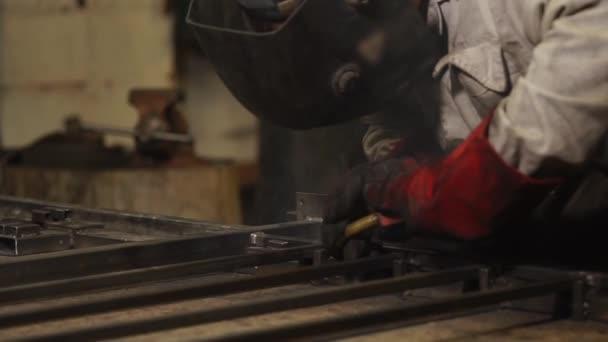 Detail svářeče během práce s kovovou konstrukcí v tovární prodejně