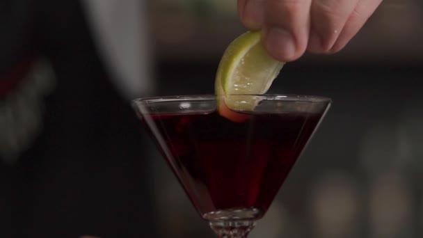 Nahaufnahme eines Glases mit einem alkoholischen Cocktail, in dem Kalk lag
