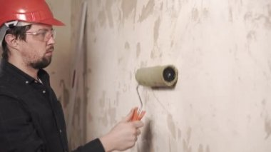 portrait of a man, a man wears a foundation under the glue on a repaired wall