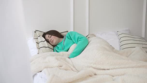 Mladá dívka je spát v posteli ráno a probouzející se