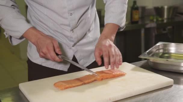 Kulinářský specialista je řezání kouskem čerstvé syrové lox na dřevěném prkénku