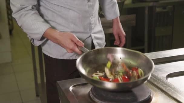 Šéfkuchař je naklánění a převrácení zeleniny na horké pánvi