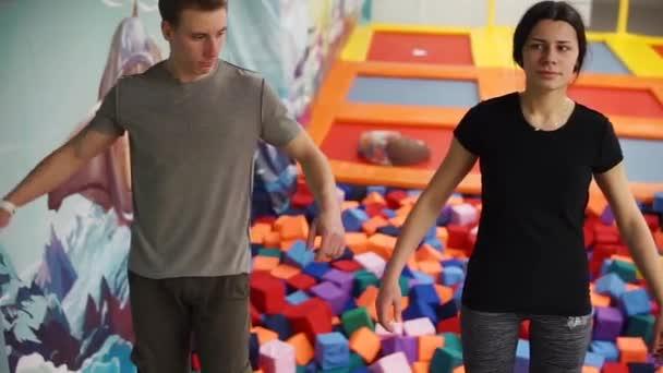 Mladý muž a žena klesá zpět do měkké kostky ve sportovní hale