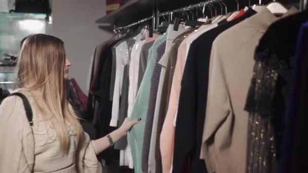 15c7446a4 Menina loira está procurando roupas em cabides na loja da moda– gráficos de  vetor