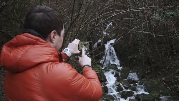 Rückansicht eines Mannes, der ein Video von einem kleinen Bach in einem Wald per Telefon aufnimmt