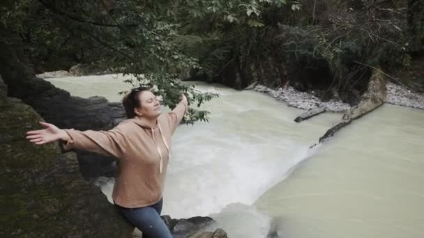 a young woman spread her hands to the sides and enjoys the waterfall