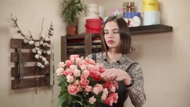 Mladá prodavačka květinový salón drží velké růže kytice