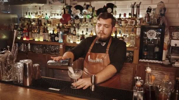 Russia Rosa Khutor - February, 2018: barman pours alcoholic cocktail into the glass