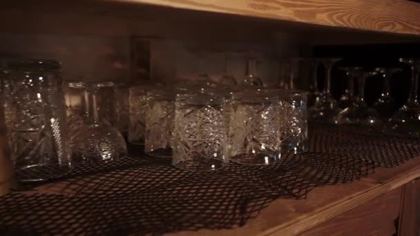 Křišťálové sklenice a poháry jsou sušeny na pultech barů, kamera se pohybuje
