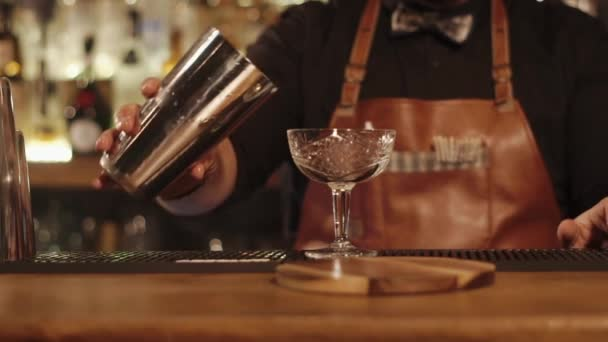 close up shot of the bartenders hands, the man pours a delicious cocktail