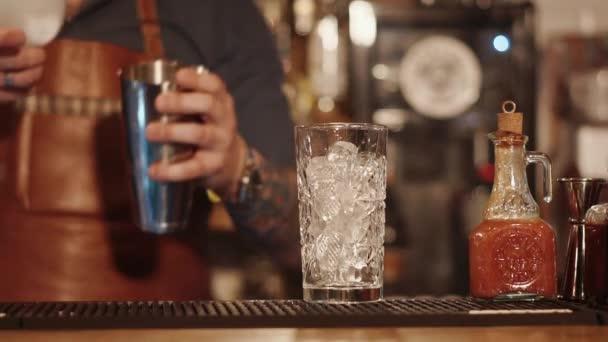 Barra rack con bicchiere alto con cubetti di ghiaccio allinterno, il barman è commovente nella priorità bassa