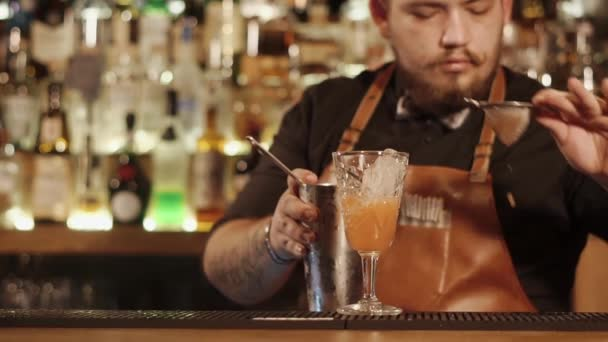 Naher Schuss auf die Hände der Barkeeper, ein Mann gießt einen Cocktail aus einem Shaker in ein Glas