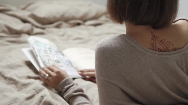Rückansicht des schlanken einsame Frau mit Tattoo im Bett mit Buch