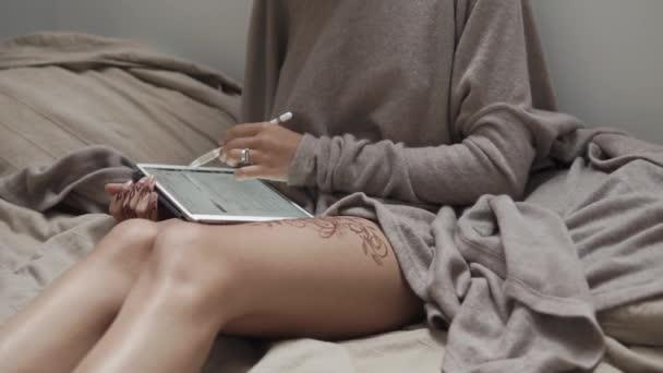 una donna con un tatuaggio del hennè sul suo piedino analizza reti sociali su una tavoletta