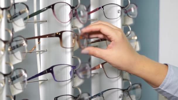 Lány vizsgálja a polcokon, optikai szalon, Szemüvegkeretek közelről