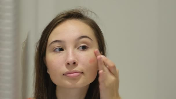 young woman is applying cream blush on cheek by fingers