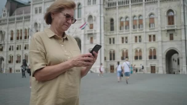Senior woman using cellphone by Parliament of Budapest, Hungary