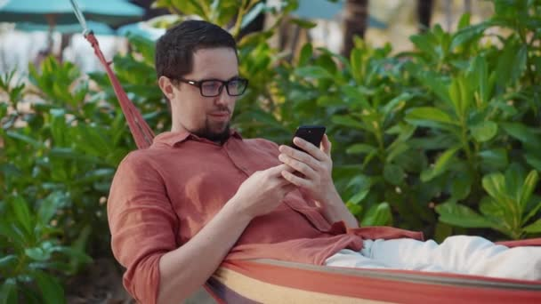 Outdoor leisure with smartphone in hammock