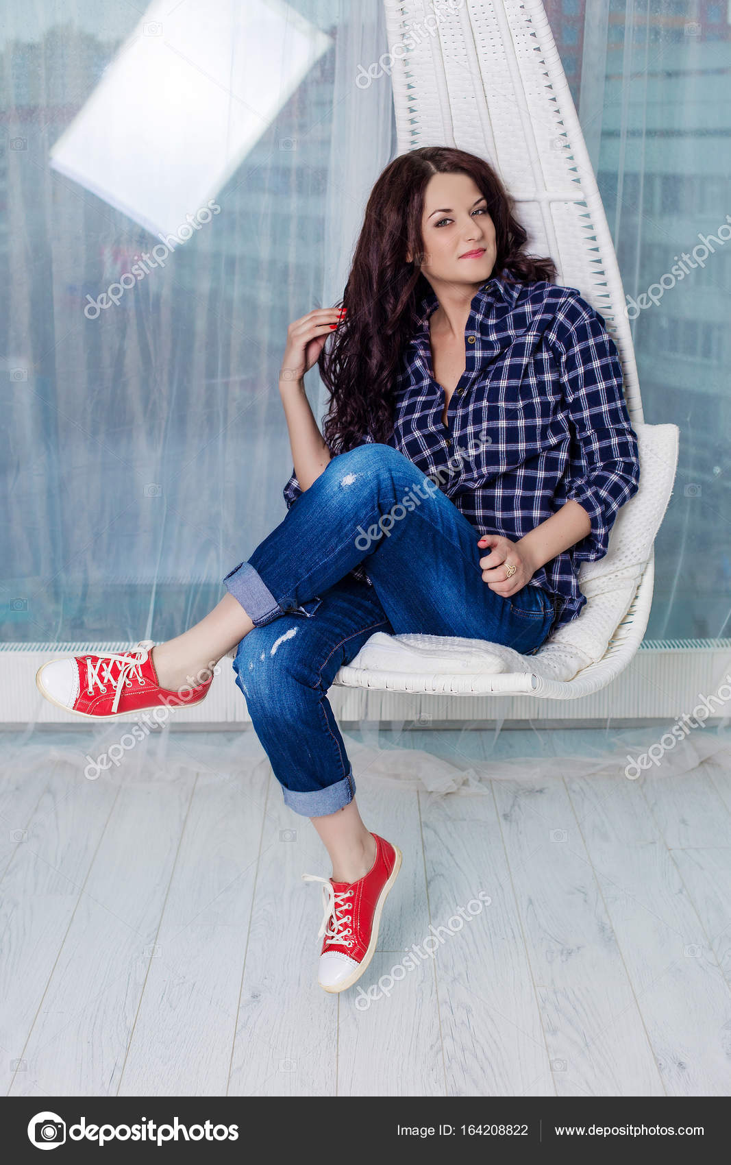 4fda797f086 Hipster girl smiling at the camera and sitting on a swing. Young caucasian  girl with dark curly hair wearing a blue plaid shirt ...
