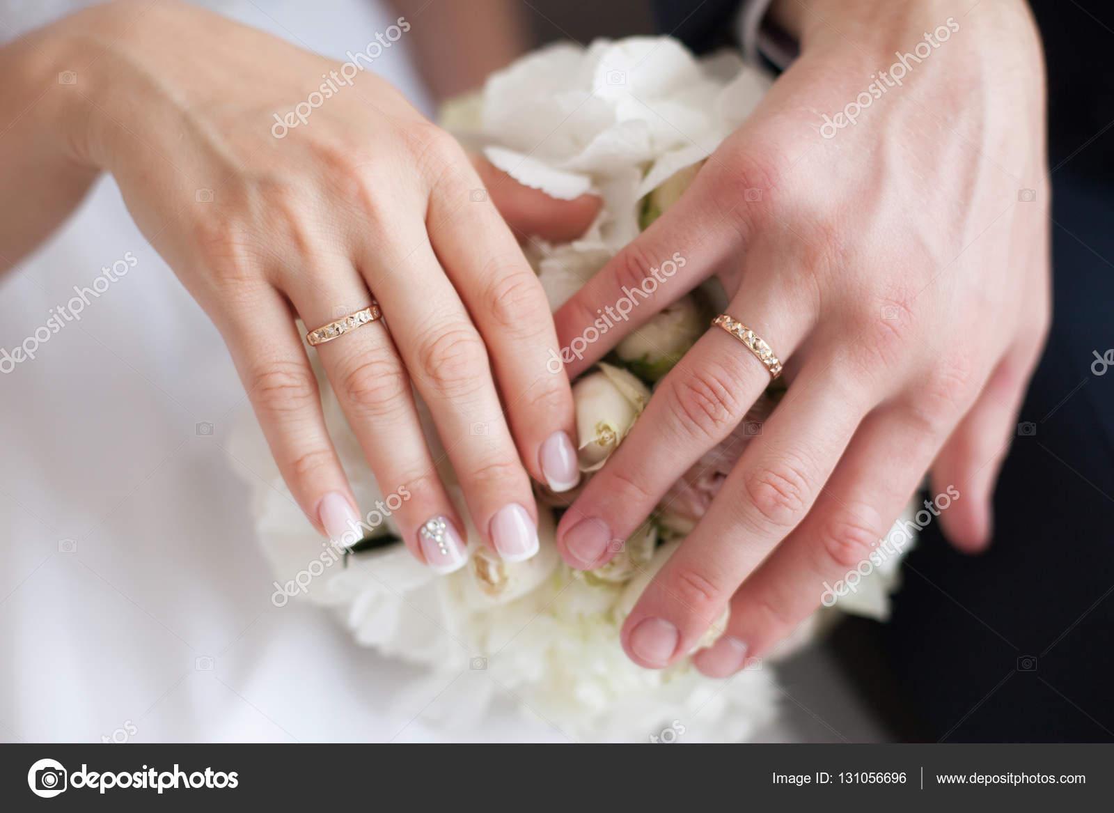 Manos de la novia y el novio en el ramo de la boda. Concepto de ...