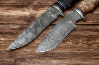 Hunting damascus steel knives handmade on wooden background