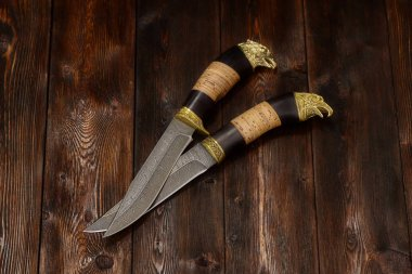 Hunting damascus steel knives handmade on a wooden background, close-up