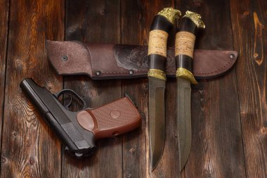 Gun and hunting damascus steel knives on a wooden background