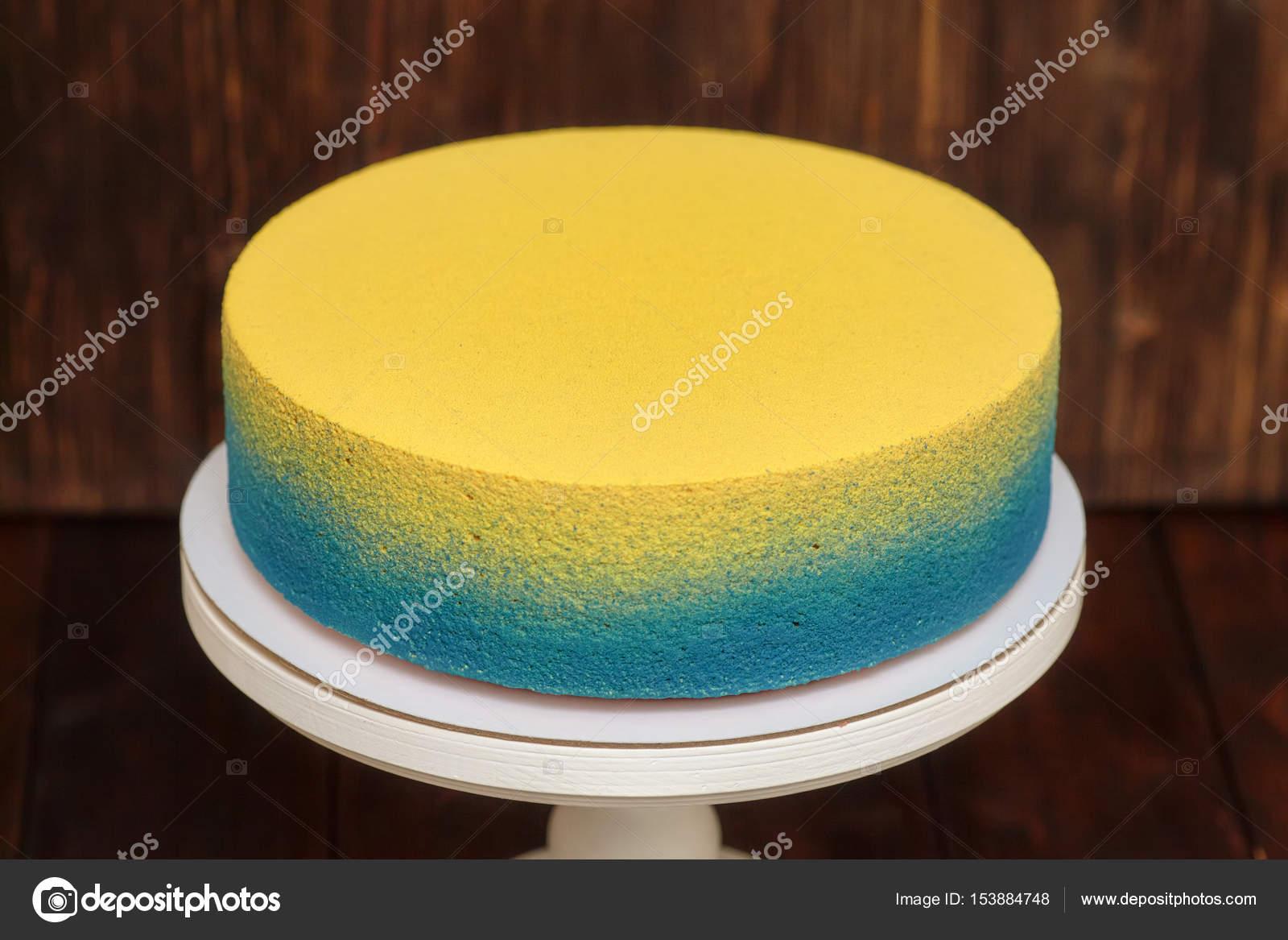 Blaue Und Gelbe Kuchen Am Stand Uber Holzerne Hintergrund