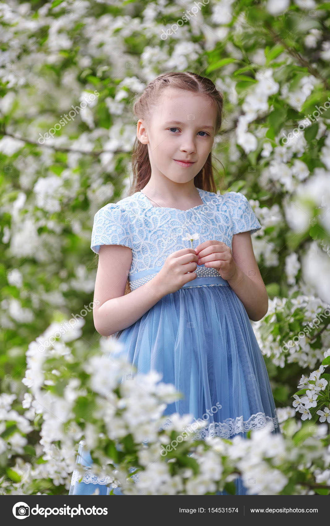 cute little girl in blooming apple tree garden at spring — stock