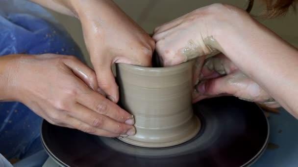 Rukou dvou lidí vytvořit hrnec, hrnčíři kola. Výuka keramiky