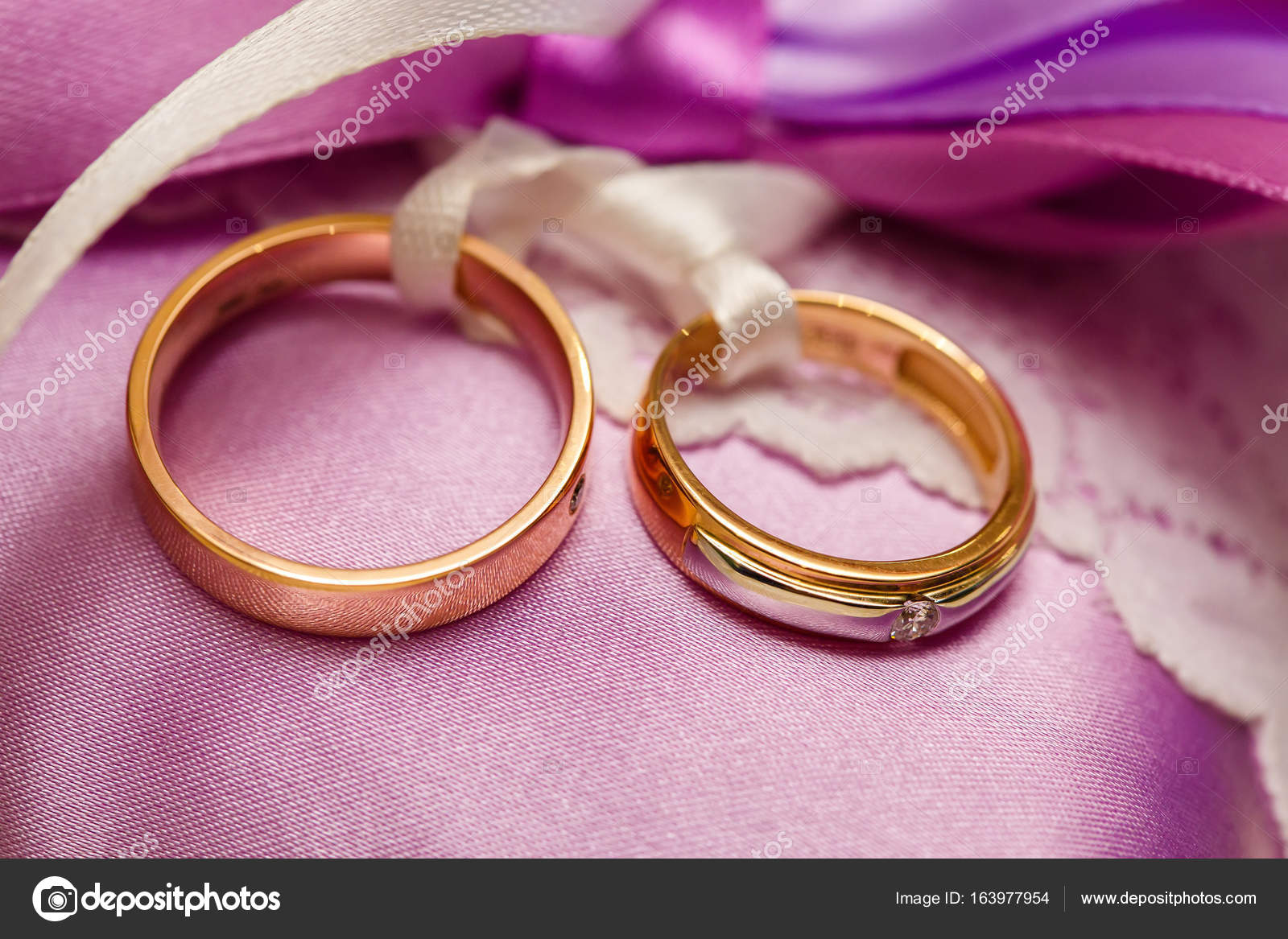 Golden wedding rings on the purple lace pillow. Marriage concept ...
