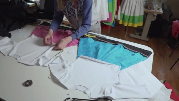 Clothing designer is working with measurements on a studio table.