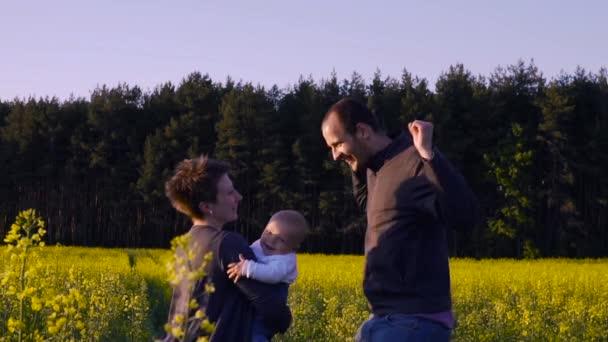 matka, otec a syn tančí a hraje v poli řepky
