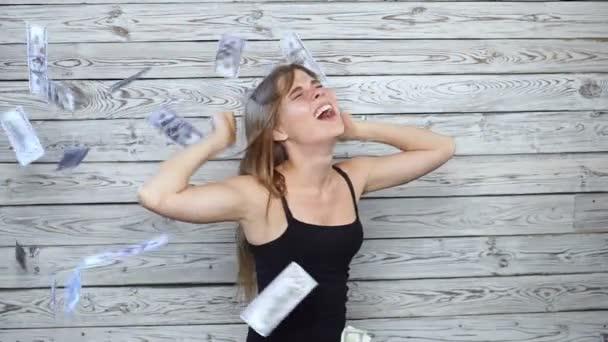 mladá žena je šťastná s klesající peníze