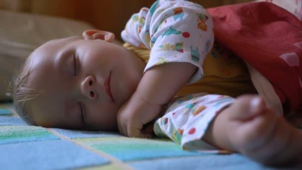Porträt eines schlafenden und aufwachenden Babys im Bett