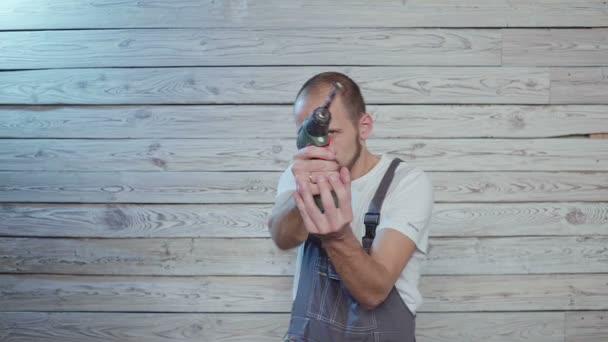 mladý muž s vrtačkou okolo, střílí