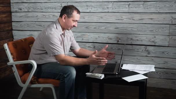 50 Jahre alter Mann mit Laptop empfangen von negativen Nachrichten, verärgert und überrascht
