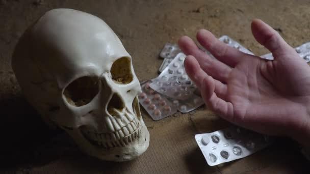 Lebka, tablety a rukou mrtvé osoby