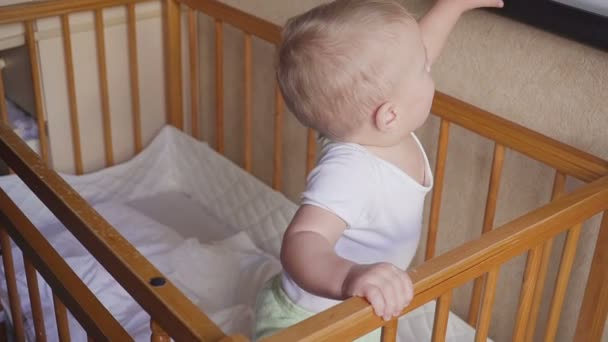 Dítě v postýlce vypadá kolem mluví, skoky a usmívá se