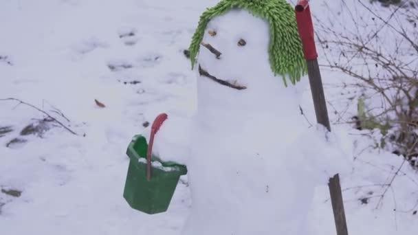 Cute usmívající se sněhulák na zelenou čepici