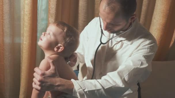 Der Arzt besucht den Säugling zu Hause. Glückliches Baby mit Stethoskop