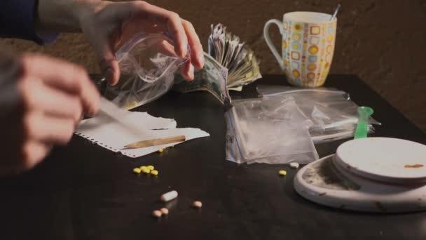 Drogový dealer balení léků - amfetamin tablety nebo jiné - v balíčcích a váží je.