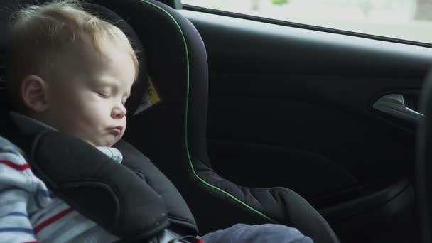 Dítě spí v autě v cestě. Spící dítě na zadní židle v autě v pomalém pohybu. HD