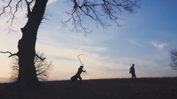 Der Sensenmann suchte sich ein neues Opfer und folgt dem Opfer, dem Mann, doch der Mann läuft davon. Sonnenuntergang Silhouette. Konzept des Todes und Kampf ums Überleben