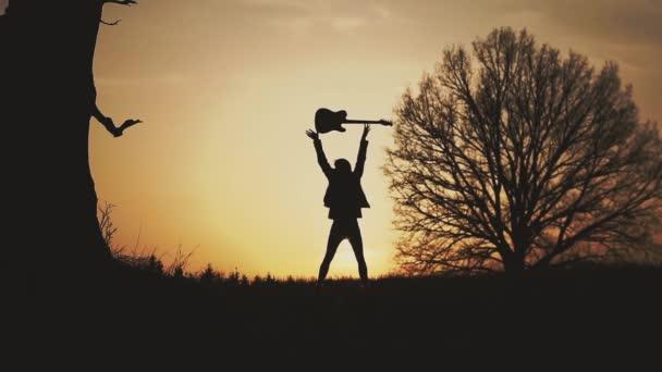Sagoma del chitarrista al tramonto rallentatore. getta la chitarra