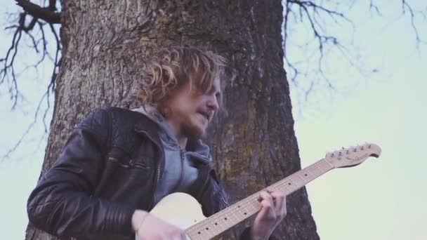 man plays electric guitar and sings a lyric song in a field near the tree at sunset