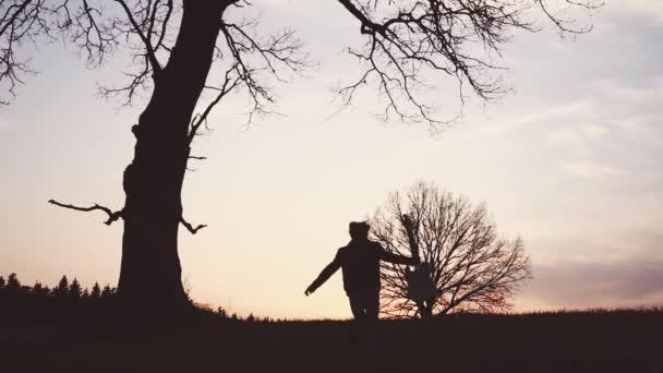 Sziluettjét gitárosa naplemente lassított. egy gitárral a kezében fut