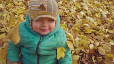 Laughing boy playing with falling leaves in park. slow motion